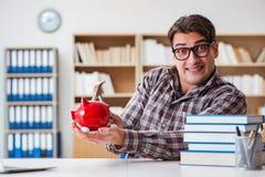 El estudiante que rompe el piggybank para pagar matrículas Imagen de archivo libre de regalías