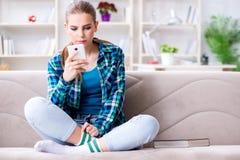 El estudiante que se sienta en el sofá con el móvil Imagenes de archivo