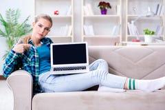 El estudiante que se sienta en el sofá con el ordenador portátil Fotos de archivo libres de regalías