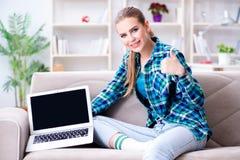 El estudiante que se sienta en el sofá con el ordenador portátil Imagen de archivo libre de regalías