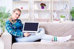 El estudiante que se sienta en el sofá con el ordenador portátil Foto de archivo libre de regalías
