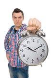 El estudiante que sostiene el despertador aislado en blanco Imagen de archivo libre de regalías