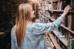 El estudiante rubio joven está eligiendo un libro del estante Ella necesita encontrar el libro derecho para prepararse al examen Foto de archivo libre de regalías