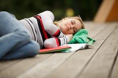 El estudiante se cae dormido para leer los libros de texto Imagen de archivo libre de regalías