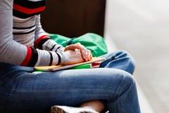El estudiante se sienta en el libro de texto del banco en manos del verano Fotografía de archivo libre de regalías