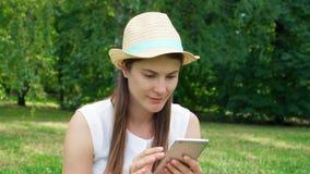 El estudiante se sienta en hierba en campus de la universidad con el móvil Charla turística en el teléfono móvil en parque públic metrajes