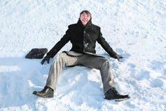 El estudiante se sienta en nieve Fotos de archivo