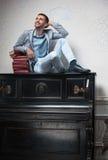 El estudiante se sienta en un piano vertical con los libros Fotografía de archivo libre de regalías