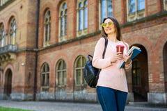 El estudiante sonriente con el bolso y se lleva el café en jardín del campus Fotos de archivo