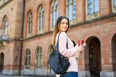 El estudiante sonriente con el bolso y se lleva el café en jardín del campus Imagenes de archivo