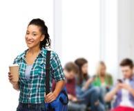 El estudiante sonriente con el bolso y se lleva la taza de café Foto de archivo