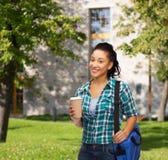 El estudiante sonriente con el bolso y se lleva la taza de café Fotografía de archivo libre de regalías