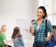El estudiante sonriente con el bolso y se lleva la taza de café Imagen de archivo