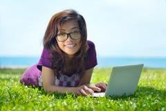 El estudiante sonriente joven está implicado con el ordenador portátil en la hierba verde Fotos de archivo libres de regalías