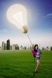 El estudiante sostiene la bombilla brillante en el campo Imagen de archivo