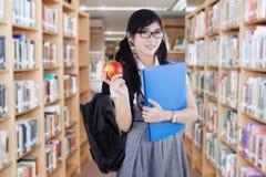 El estudiante sostiene la manzana en biblioteca Imagen de archivo