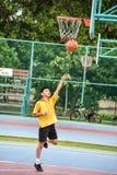 El estudiante tailandés está haciendo un lanzamiento del layup en cancha de básquet pública Fotografía de archivo