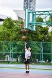 El estudiante tailandés está haciendo un lanzamiento del layup en cancha de básquet pública imágenes de archivo libres de regalías