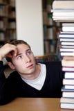 El estudiante tensionado mira la pila del libro Fotografía de archivo