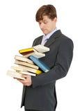 El estudiante tiene gran manojo de libros de textos Imagen de archivo
