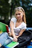 El estudiante toma el libro que se sienta en banco al aire libre Foto de archivo libre de regalías