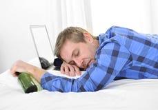 El estudiante trabajó demasiado dormido en el ordenador que sostenía la botella de cerveza Fotografía de archivo libre de regalías