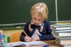 El estudiante trabaja en una sala de clase de la escuela, niño en la escuela, Foto de archivo