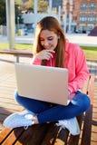 El estudiante a una sonrisa hermosa y a un pelo rubio largo, vino al parque, se está preparando para los exámenes Imagen de archivo