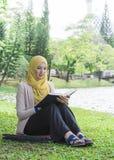 El estudiante universitario bonito goza el leer en el parque Foto de archivo libre de regalías
