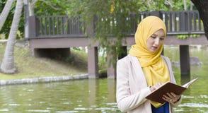 El estudiante universitario bonito goza el leer en el parque Fotografía de archivo libre de regalías