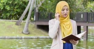 El estudiante universitario bonito goza el leer en el parque Imagenes de archivo