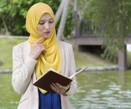 El estudiante universitario bonito goza el leer en el parque Fotos de archivo