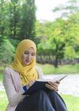 El estudiante universitario bonito goza el leer en el parque Imagen de archivo libre de regalías