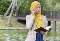 El estudiante universitario bonito goza el leer y el pensar en el parque Imagenes de archivo