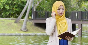 El estudiante universitario bonito goza el leer y el pensar en el parque Imágenes de archivo libres de regalías