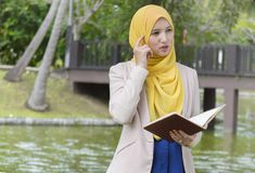 El estudiante universitario bonito goza el leer y el pensar en el parque Fotografía de archivo libre de regalías