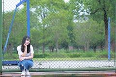El estudiante universitario chino asiático disfruta de tiempo libre en el campus Imagen de archivo libre de regalías