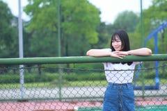 El estudiante universitario chino asiático disfruta de tiempo libre en el campus foto de archivo libre de regalías
