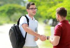 El estudiante universitario con los vidrios encuentra a su amigo en el parque de la universidad y Imágenes de archivo libres de regalías