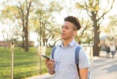 El estudiante universitario hispánico habla en el smartphone con auriculares de botón imágenes de archivo libres de regalías
