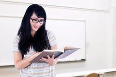 El estudiante universitario lee un libro mientras que se coloca Imagenes de archivo