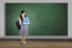 El estudiante universitario sostiene la fruta de la manzana en clase Fotografía de archivo