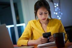 El estudiante universitario Studying At Night mecanografía el mensaje en el teléfono Fotografía de archivo libre de regalías