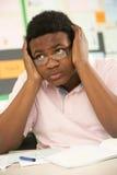 El estudiar adolescente masculino tensionado del estudiante Fotos de archivo libres de regalías