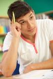 El estudiar adolescente masculino tensionado del estudiante Foto de archivo libre de regalías
