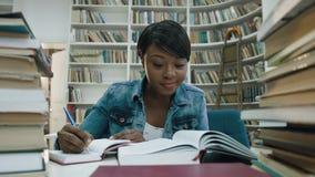El estudiar africano del estudiante, haciendo algunas notas del libro rodeado por los libros en la biblioteca moderna almacen de metraje de vídeo