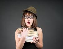 El estudiar de la muchacha del empollón Educación Estudiante en vidrios divertidos con los libros en gris Foto de archivo