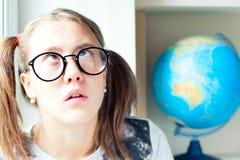 El estudiar de molestia La muchacha nerdy divertida en lentes cansó de pasto Imagen de archivo