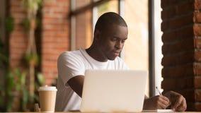 El estudiar de trabajo del hombre afroamericano serio con el ordenador portátil que hace notas fotos de archivo libres de regalías