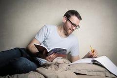 El estudiar en cama Imagen de archivo libre de regalías